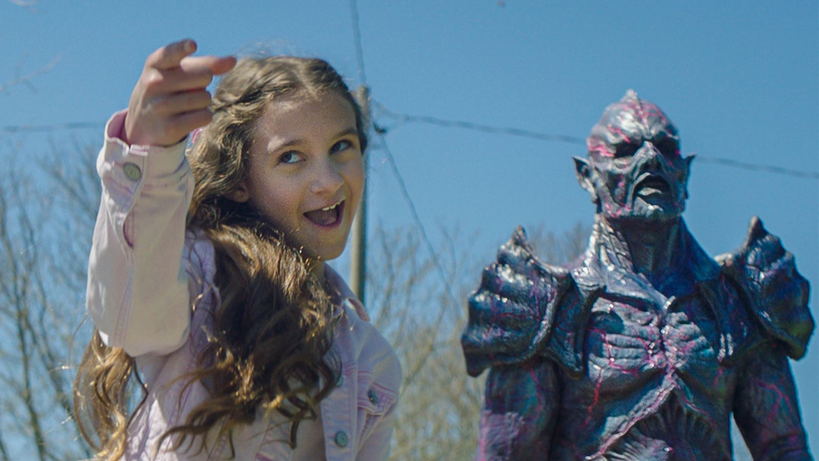 little girl points, smiling, with monster behind her